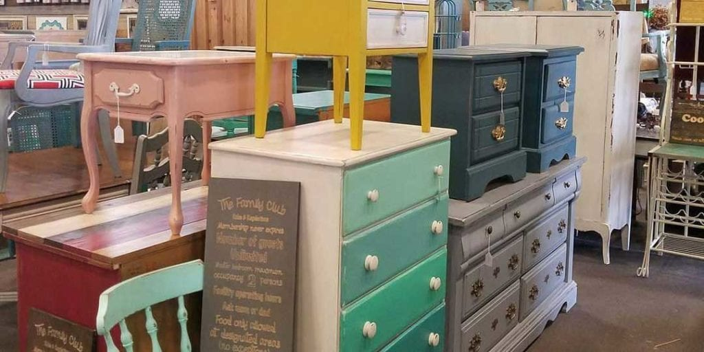A collection of different colored furniture, including a painted dresser