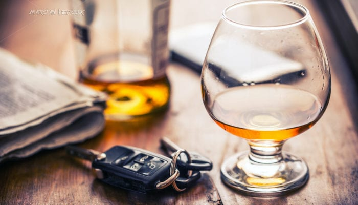 photo of car keys resting on a table next to a snifter of alcohol. DUI Lawyer